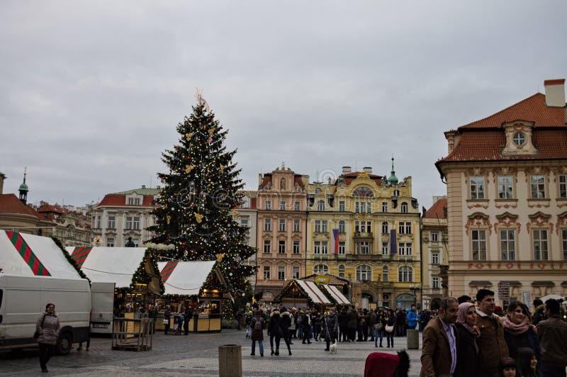 Praag, Tsjechië: mensen die op het Oude Town-plein wandelen bij de kerststand en de kerstboom royalty-vrije stock afbeelding