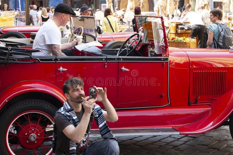 Praag, Tsjechische Republiek - 20 April, 2011: De bestuurder van een rode uitstekende auto die een krant in afwachting van passag stock foto