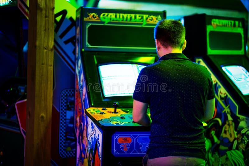 PRAAG - TSJECHISCHE REPUBLIEK, 5 Augustus, 2017 - Jonge mens die een oud uitstekend arcadespel spelen royalty-vrije stock afbeelding