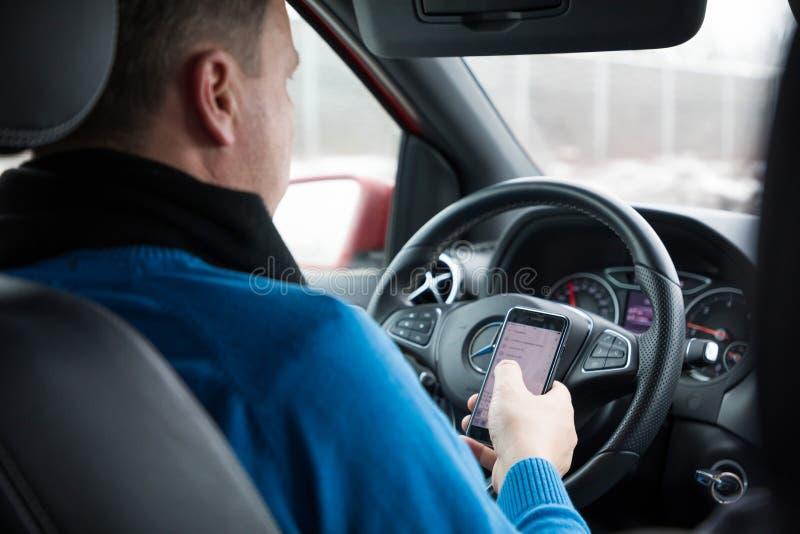 Praag, Tsjechische Republiek - 21 01 1018: Mens die slimme telefoon in auto met behulp van tijdens het drijven stock foto