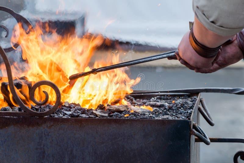 Praca blacksmith z metalem ogieniem zdjęcia stock
