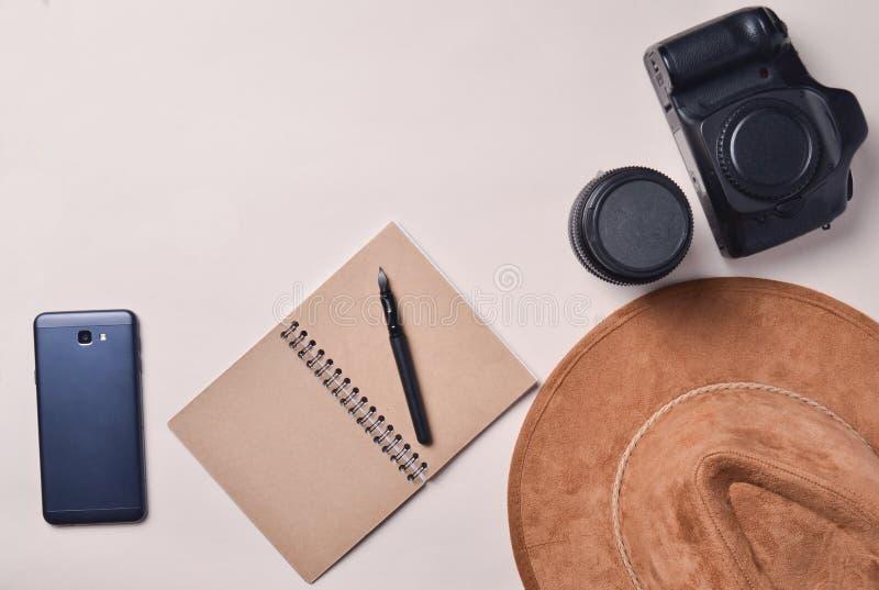 Praca fotoreporter Smartphone, notatnik, kapelusz, kamera, obiektyw Podróżuje pojęcie, odgórny widok, mieszkanie nieatutowy obrazy stock