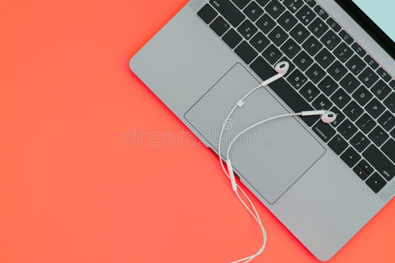 Praca na laptopie z muzyką Nowożytny ładny notatnik i biali hełmofony na czerwonym tle zdjęcie stock