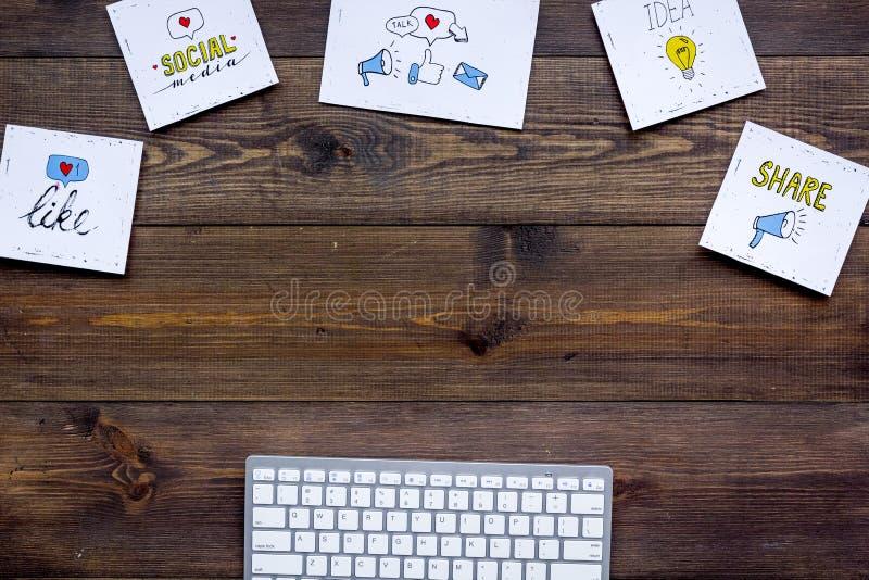 Praca w ogólnospołecznych środkach Medialny marketing Biurko z klawiatury i socail środków ikonami Ciemna drewniana tło odgórnego obrazy stock