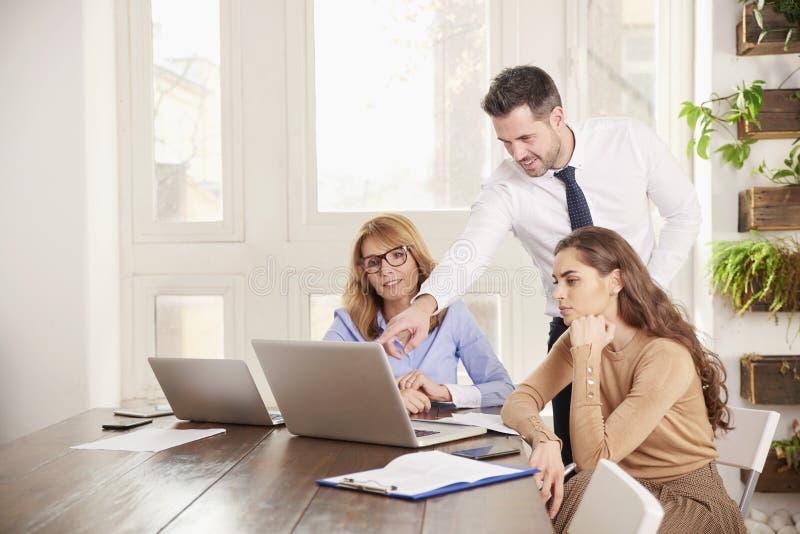 Praca zespo?owa w biurze Grupa ludzie biznesu pracuje wp?lnie na laptopie w biurze zdjęcie stock