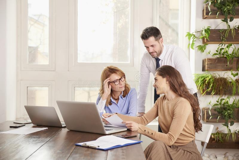Praca zespo?owa w biurze Grupa ludzie biznesu pracuje wp?lnie na laptopie w biurze fotografia stock