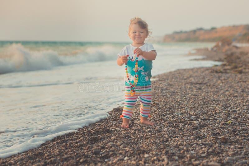 Prachtig droombeeld van babymeisje met blonde haren blauwe ogen en roze wangen die het lopen aan overzeese van het zandstrand par stock afbeeldingen