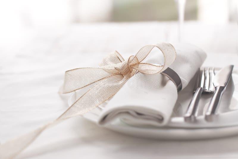 Prachtig elegante verfraaide lijst voor vakantie - huwelijk of valentijnskaartdag met moderne bestek, boog, glas, kaars en gift stock foto