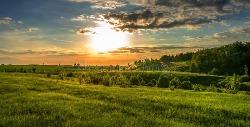 Prachtig landschap, zonsondergang over gebieden, ravijnen en bossen, turkooise oranje hemel en heldergroene gras en bladeren van  royalty-vrije stock afbeelding