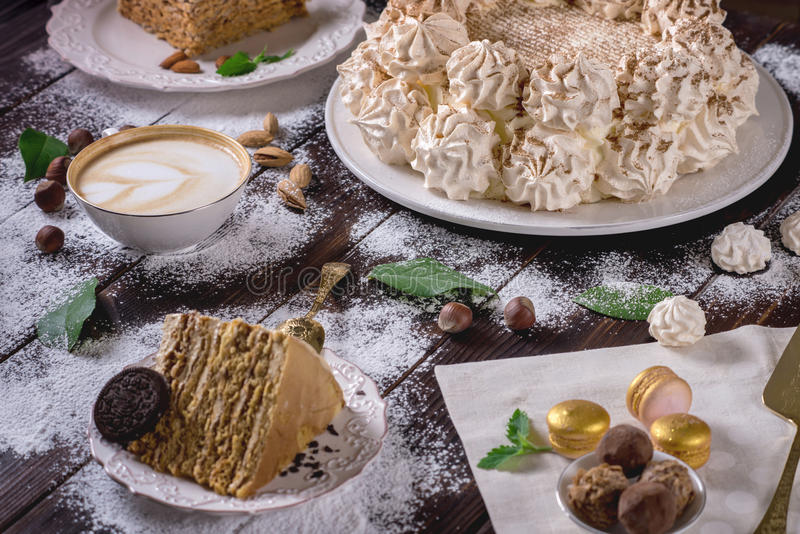 Prachtig verfraaide dessertlijst waar de cake met schuimgebakje op een donkere houten lijst Regeling van heerlijke snoepjes stock afbeeldingen