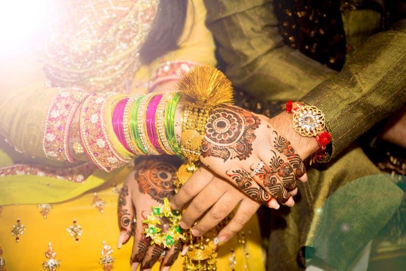 Prachtig verfraaide Indische bruidhanden met de bruidegom stock fotografie