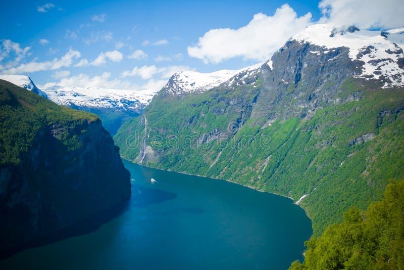Prachtige Geiranger-Fjord noorwegen Het is een fairytalelandschap met zijn majestueuze, snow-covered bergbovenkanten, wild en moo stock fotografie