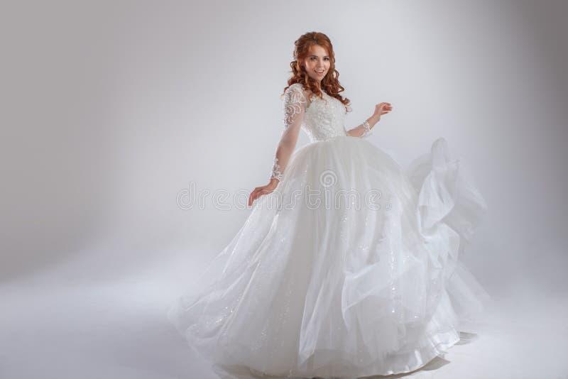 Prachtige huwelijkskleding met een hoepelrok, klassieke stijl vrouwenbruid in overvloedige huwelijkskleding Lichte achtergrond stock foto
