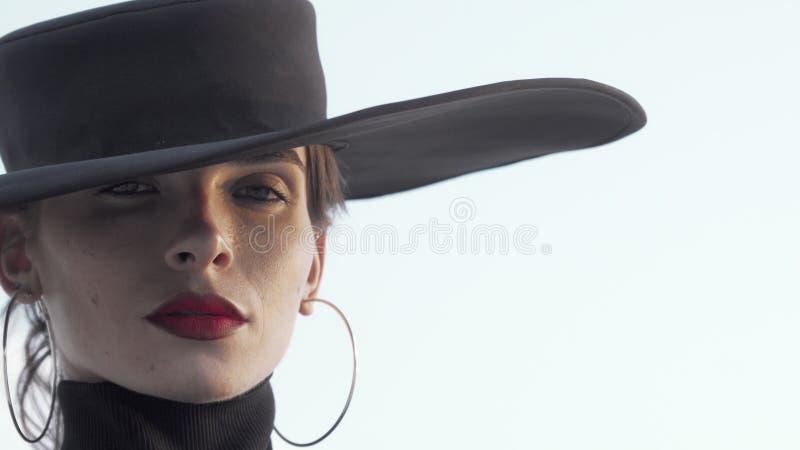 Prachtige, rode, lichtzinnige vrouw met zwarte hoed die doordacht wegkijkt royalty-vrije stock afbeelding