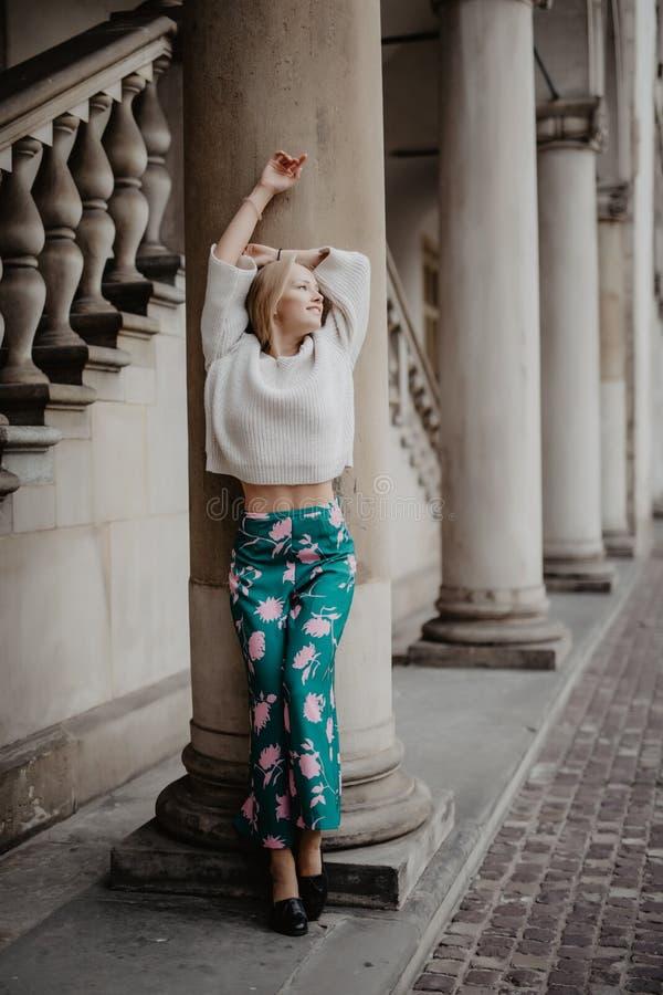 Prachtige schoonheidsvrouw die en dichtbij kolom stellen glimlachen en camera in de straat bekijken stock fotografie