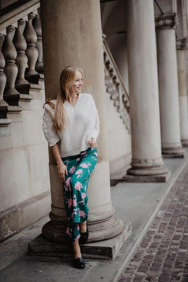 Prachtige schoonheidsvrouw die en dichtbij kolom stellen glimlachen en camera in de straat bekijken royalty-vrije stock fotografie