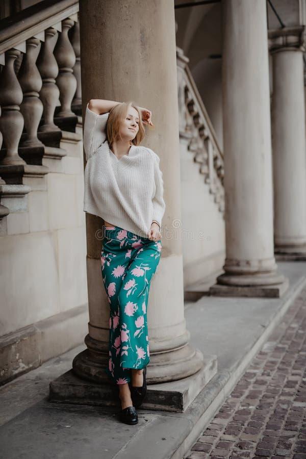 Prachtige schoonheidsvrouw die en dichtbij kolom stellen glimlachen en camera in de straat bekijken royalty-vrije stock afbeeldingen