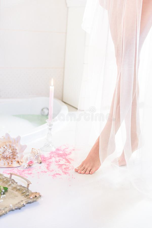 Prachtige vrouwelijke die benen in een transparant wit gordijn worden verborgen stock foto