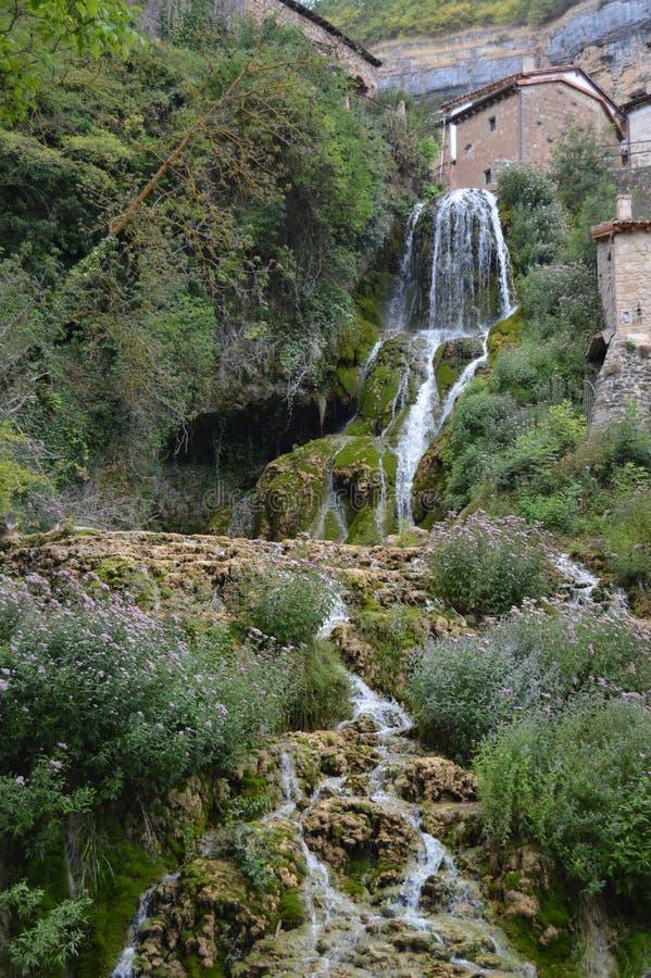 Prachtige Watervallen met Zijdeeffect van een Kristallijn Groenachtig Water dat tussen de Huizen loopt en in de Ebro Rivier toevl stock afbeeldingen