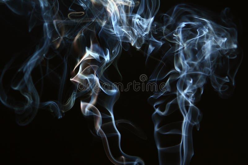 Prachtige wervelings lichtblauwe rook tegen zware zwarte achtergrond stock foto's