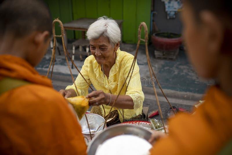 Prachuap Khiri Khan Thailand - june2,2019: ?r erbjudande mat f?r den thai kvinnan till den thai munken p? ottan, buddhism den huv royaltyfria foton