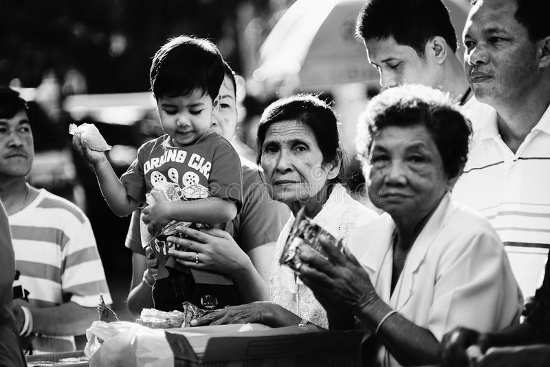 Prachuapkhirikhan, Tailandia - 16 de noviembre de 2015: Niño no identificado y mujer mayor del budista para hacer mérito fotografía de archivo libre de regalías