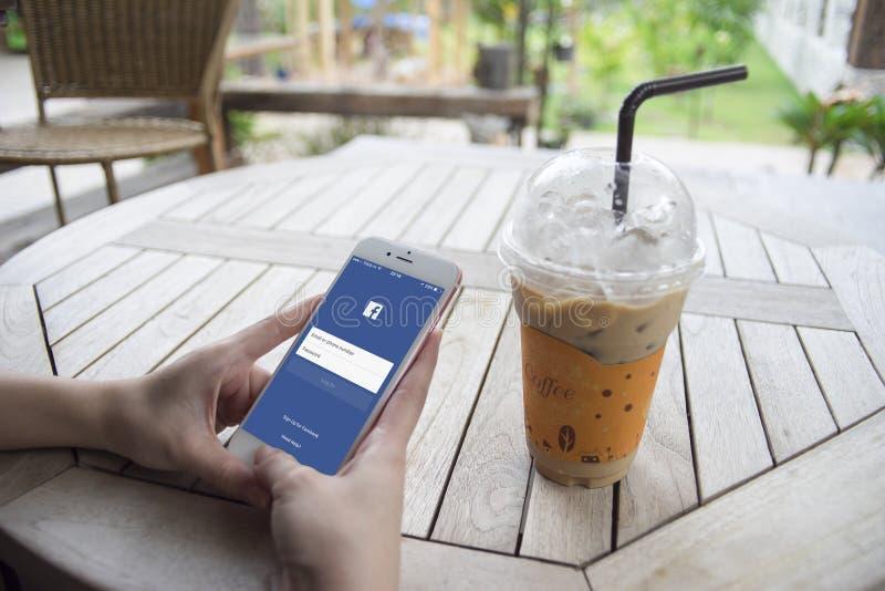 Prachuapkhirikhan, Thailand-herrliche 6,2016: Frauenhand, die einen Smartphone mit Facebook-Seite auf Schirm, am Kaffeecafé hält lizenzfreies stockbild