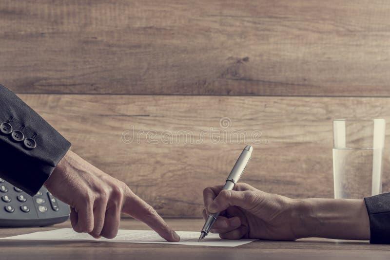 Pracodawca pokazuje jego pracownikowi gdzie podpisywać kontrakt zdjęcia royalty free