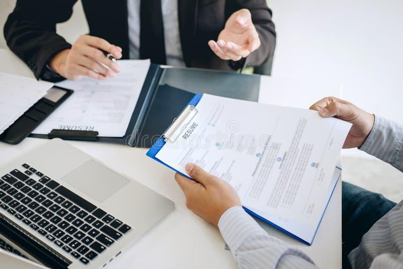 Pracodawcy lub osoby werbującej mienie czyta życiorysowi podczas colloquy wokoło jego profil kandydat, pracodawca w kostiumu prow obraz stock