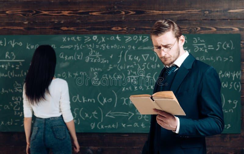 Pracować problem w algebrze zrobić sumom Nauczyciel czyta książkę dziewczyna uczeń przy chalkboard Genialny mężczyzny i kobiety t obrazy royalty free