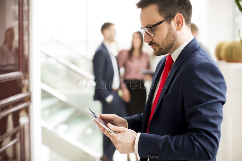 Pracowity biznesmen ubierał w kostium pozycji w nowożytnym biurze i używać pastylka obraz royalty free