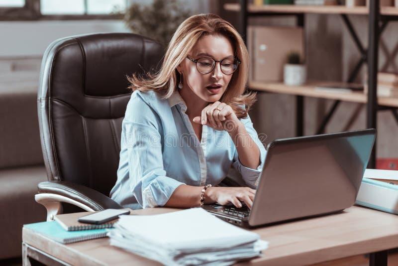 Pracowity bizneswoman jest ubranym szkła czyta znacząco emaila obrazy royalty free