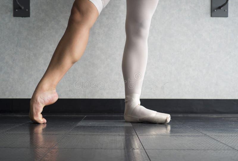 Pracowity dyscyplinujący balerina baletniczy tancerz rozgrzewkowy up w jej pointe butach zdjęcia stock