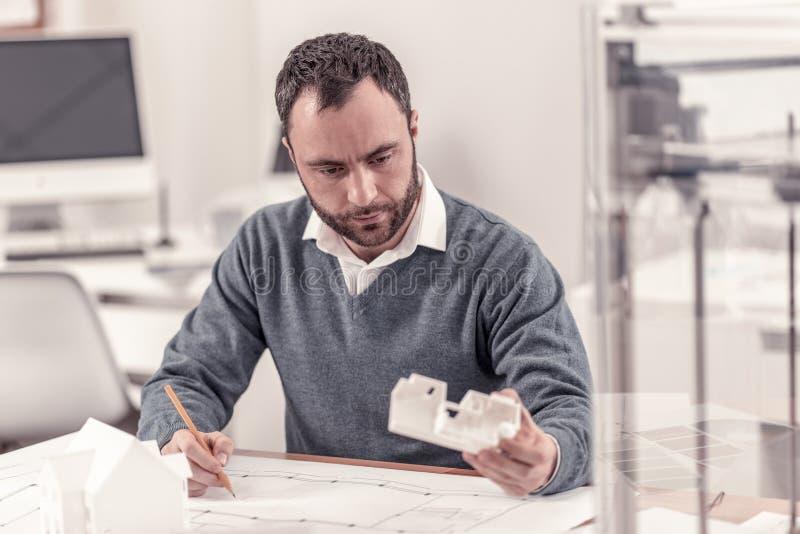 Pracowity inżynier porównuje jego rysunki z układem zdjęcie stock