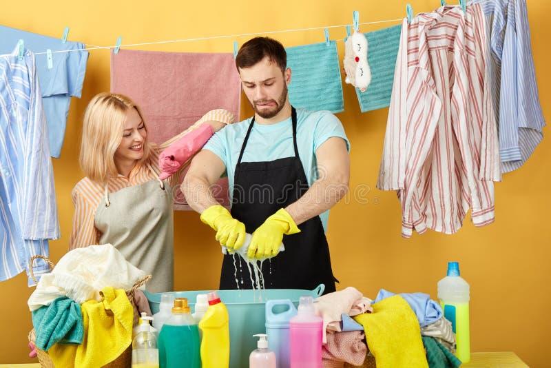 Pracowity mężczyzna gniesie za wetclothes, podczas gdy jego żona kontroluje jego praca obraz stock