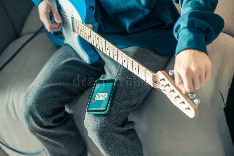 Pracowity muzyk nastraja jego instrument muzycznego i obserwuje otrzymywającą wiadomość fotografia stock