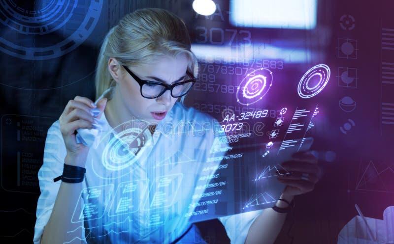 Pracowity programista trzyma jej nowożytnego przyrząd i patrzeje martwiący się zdjęcie stock