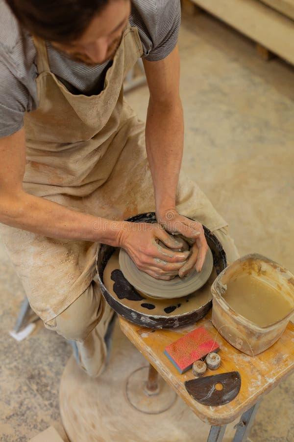 Pracowity wykwalifikowany faceta obsiadanie na drewnianej ławce z ceramicznym kołem fotografia stock