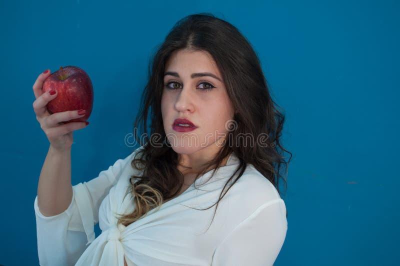 Pracowniana fotografia z śliczną dziewczyną i jabłkiem obraz royalty free