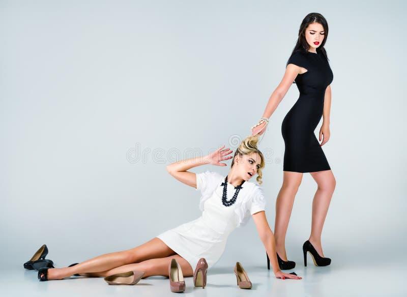 Pracowniana moda strzelająca: konfrontacja dwa ślicznej kobiety (blondynka i brunetka) zdjęcie stock