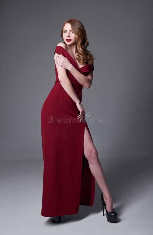 Pracowniana moda strzelająca: portret urocza młoda dziewczyna w czerwieni sukni fotografia stock