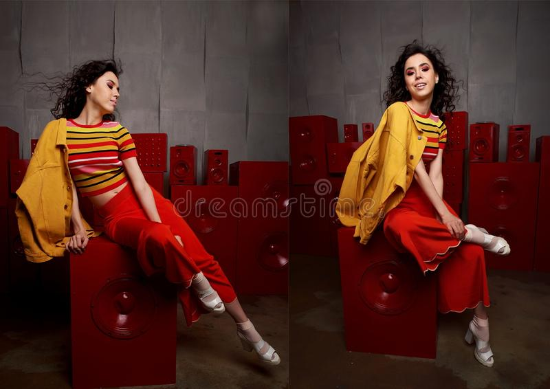 Pracowniana mody strzelanina Dziewczyna w stroju, wierzchołku i spodniach jaskrawych, migotał w czerwieni i pomarańcze brzmieniac zdjęcia stock