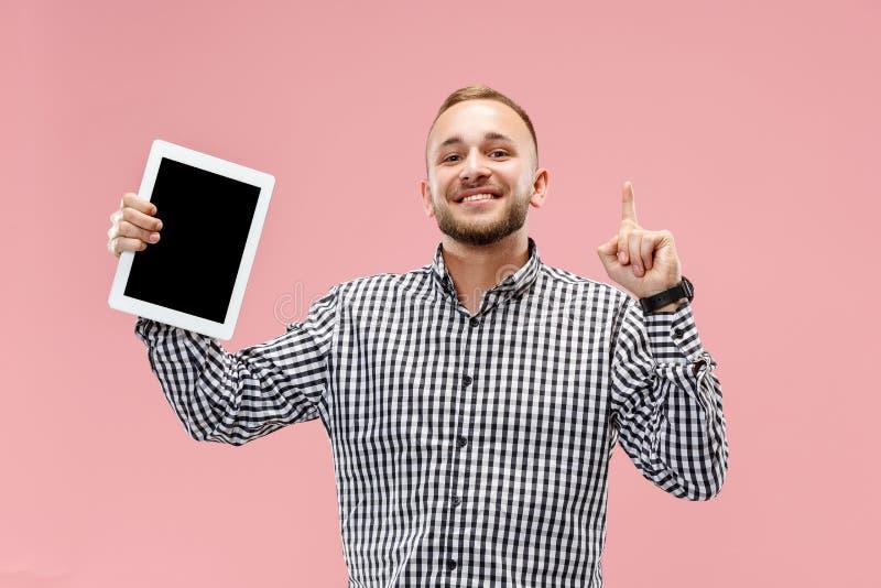 Pracowniany obrazek odizolowywający na różowej tło pozyci w przypadkowych ubraniach trzyma pastylkę i pokazuje je pozytywny mężcz obraz royalty free