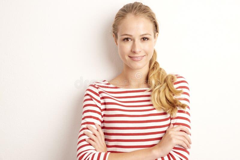 Pracowniany portret ładny młodej kobiety lookig przy kamerą i ono uśmiecha się podczas gdy stojący przy odosobnionym białym tłem  zdjęcia royalty free