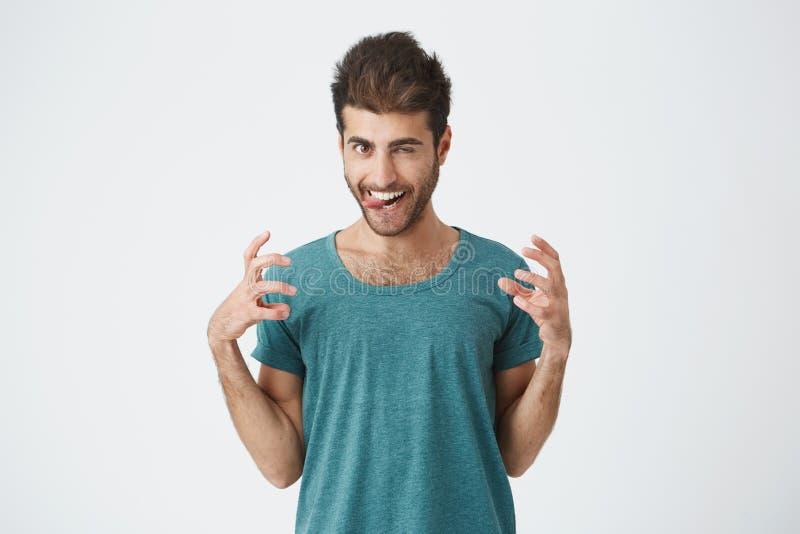 Pracowniany portret śmieszny ekspresyjny hiszpański facet w błękitnej koszulce, bawić się durnia pokazuje jęzor i zęby, mieć zaba fotografia stock