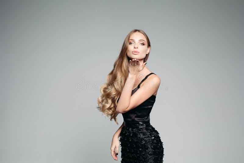 Pracowniany portret atrakcyjna blond kobieta jest ubranym eleganckiego srebro z długim gęstym włosy i profesjonalisty makijażem obrazy royalty free