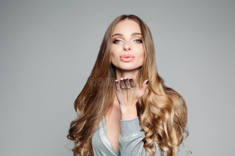 Pracowniany portret atrakcyjna blond kobieta jest ubranym eleganckiego srebro z długim gęstym włosy i profesjonalisty makijażem obraz royalty free