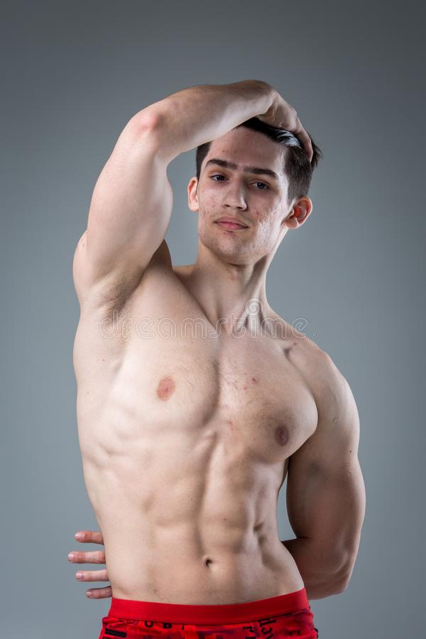 Pracowniany portret młodej brunetki caucasian mężczyzna na szary tła pozować Dojrzałość płciowa temat, problemowa skóra, nastolet zdjęcie royalty free