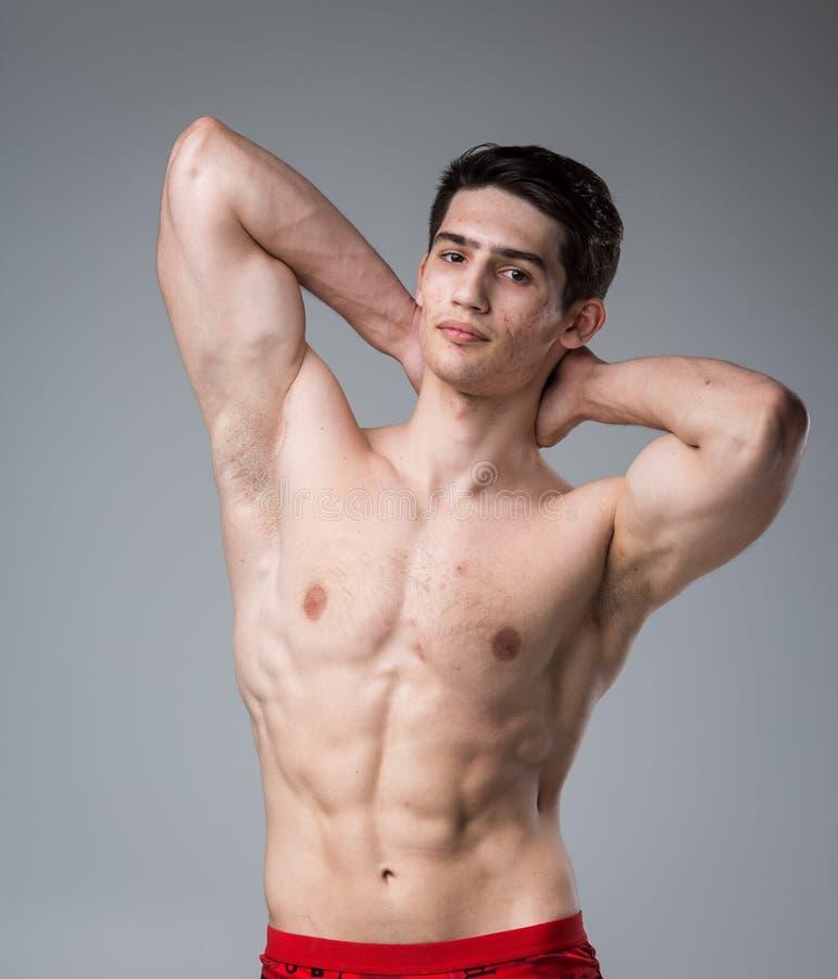 Pracowniany portret młodej brunetki caucasian mężczyzna na szary tła pozować Dojrzałość płciowa temat, problemowa skóra, nastolet zdjęcia royalty free