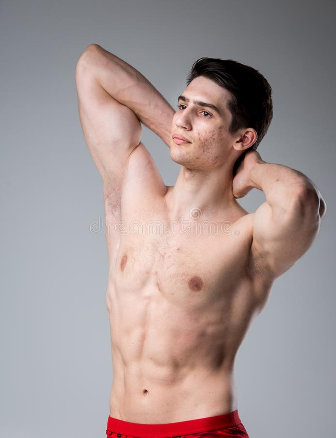 Pracowniany portret młodej brunetki caucasian mężczyzna na szary tła pozować Dojrzałość płciowa temat, problemowa skóra, nastolet zdjęcia stock